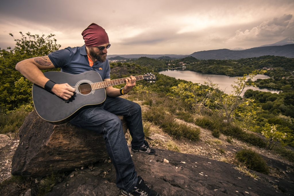 Man playing guitar on a hill