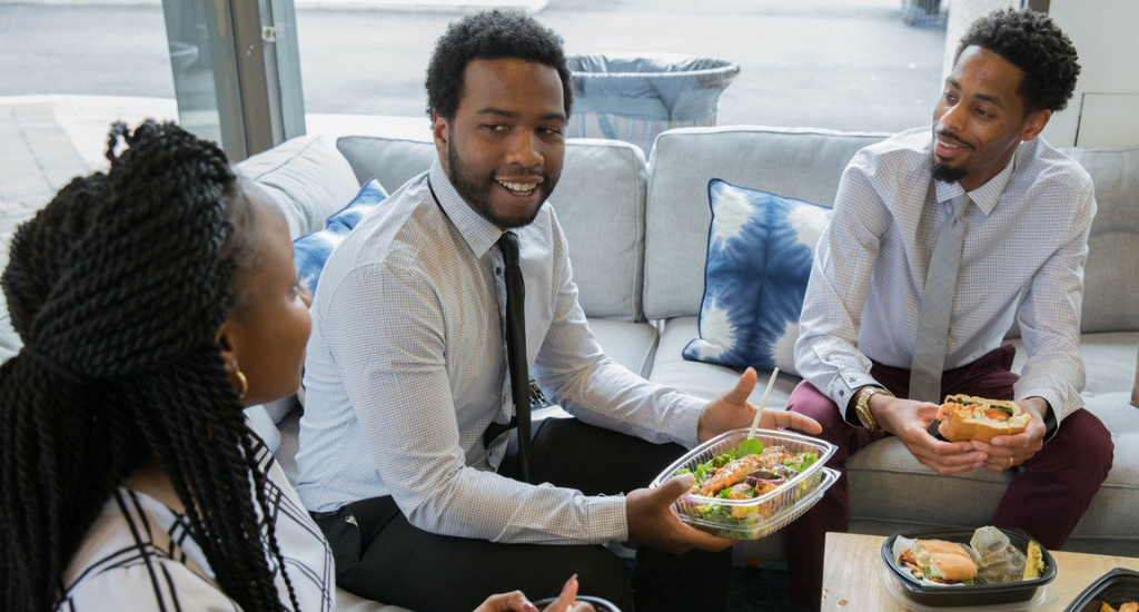 Business casual coworkers eating lunch with employer