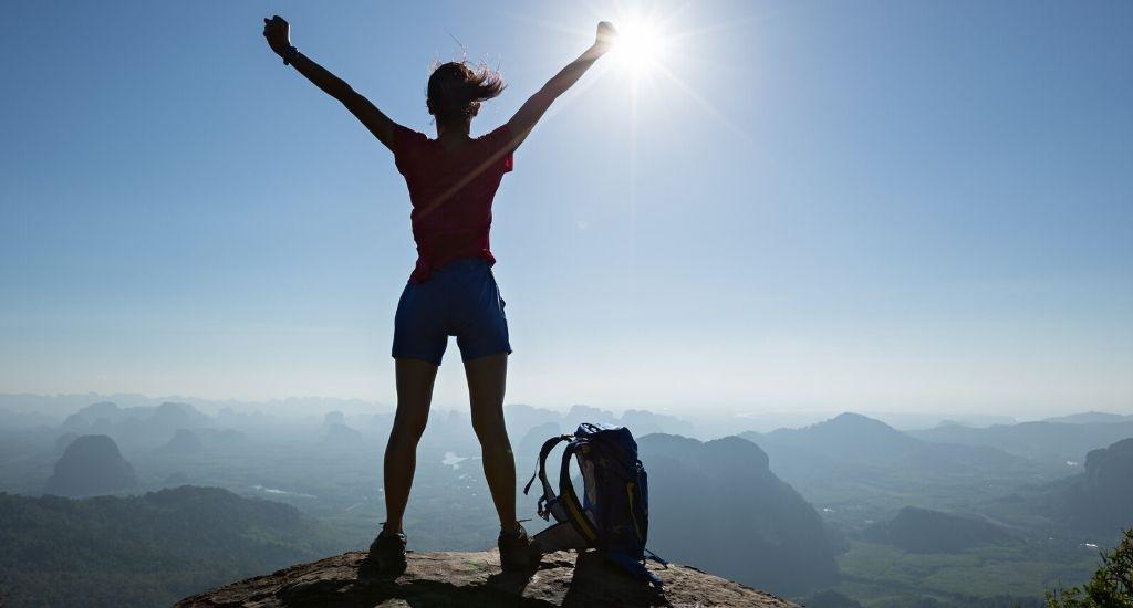 Successful entrepreneur standing on mountaintop