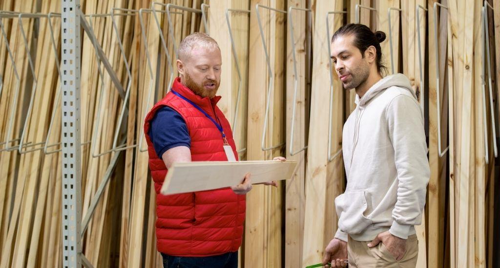 Entrepreneur showing wooden boards to customer in hardware shop